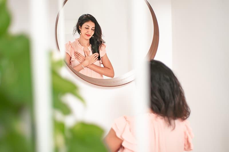 positive Frau, die ihre Hände auf Brust stützt, die vor dem Spiegel steht