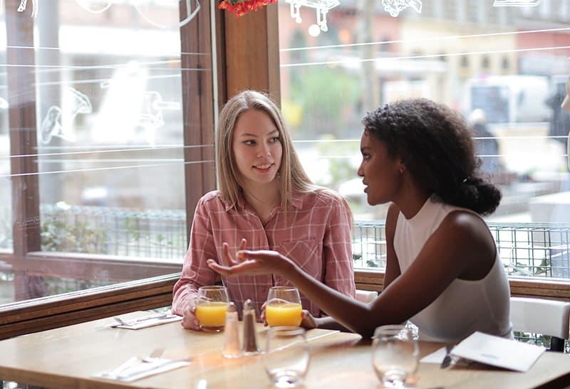 positive blonde Frau im Gespräch mit ihrer Freundin im Café