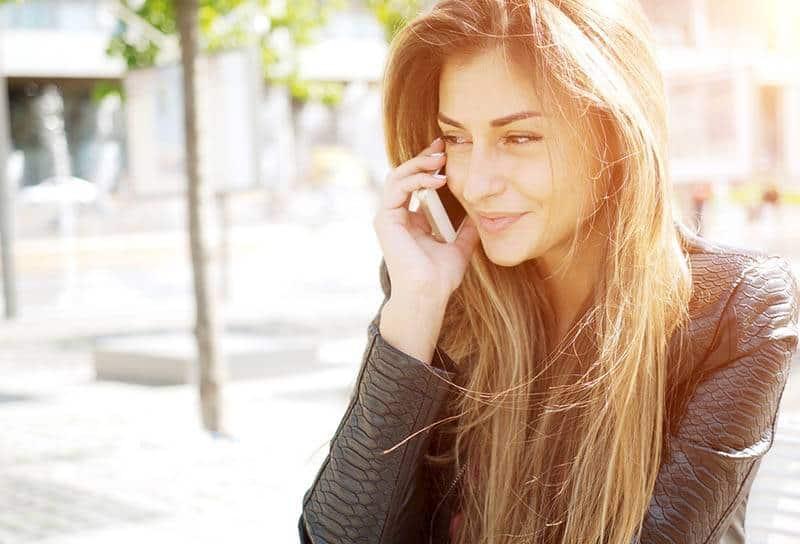 süße Frau, die am Telefon spricht