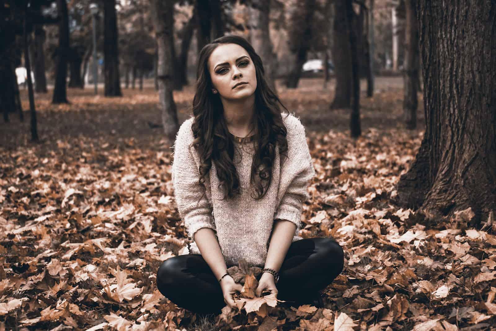 traurige Frau, die auf trockenen Blättern im Park sitzt