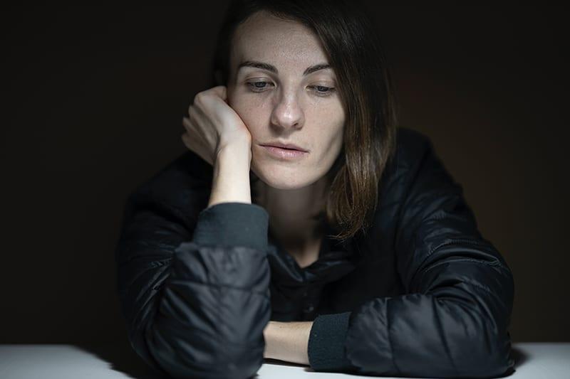 traurige Frau, die sich auf ihre Hand stützt, die am Tisch sitzt