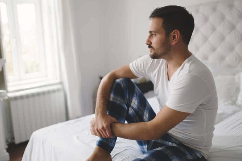 unglücklicher Mann im Pyjama auf dem Bett