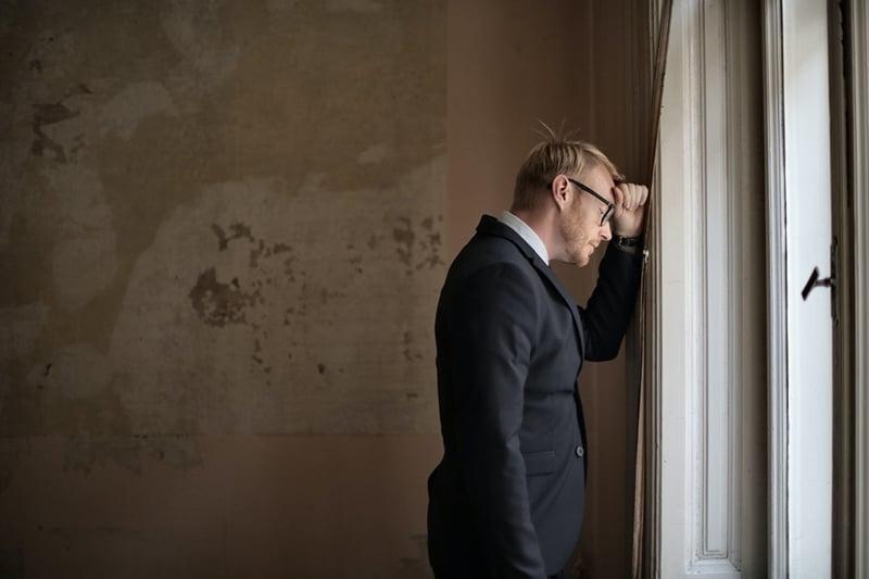 verzweifelter Unternehmer, der sich an die Wand in der Nähe des Fensters lehnt