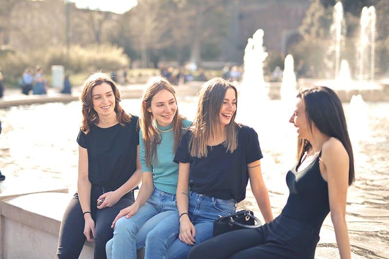 vier lächelnde Freundinnen, die sprechen, während sie auf dem Brunnen sitzen