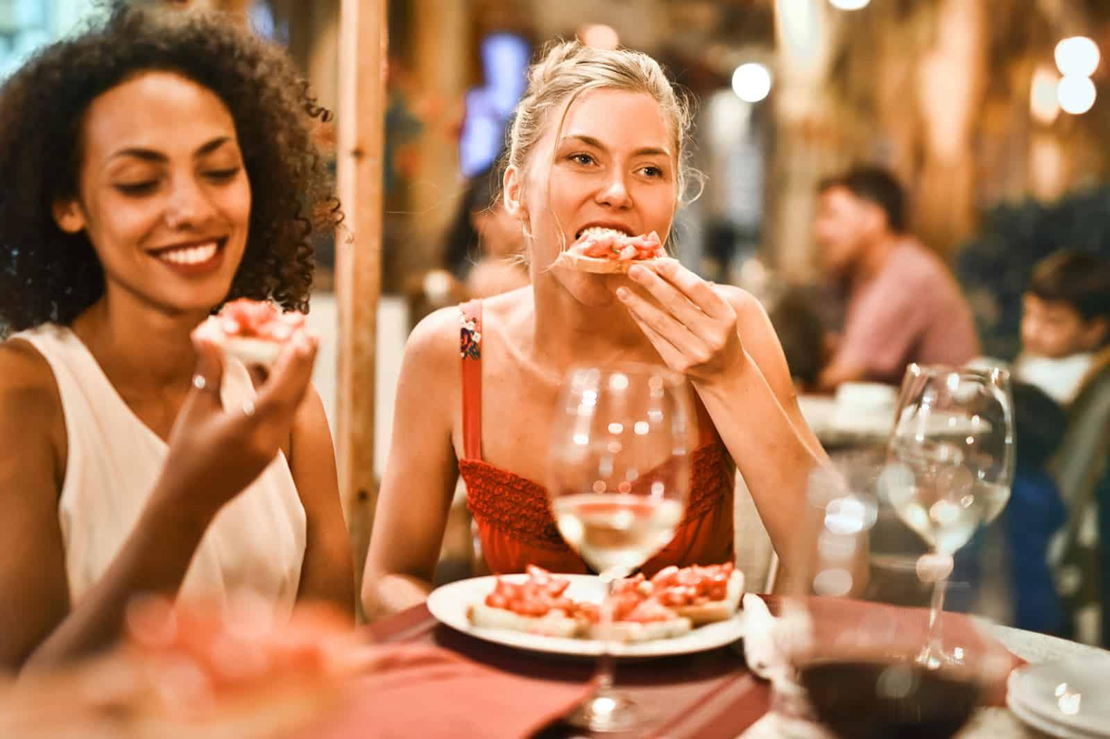 zwei Freundinnen, die in einem Restaurant essen, während sie abhängen
