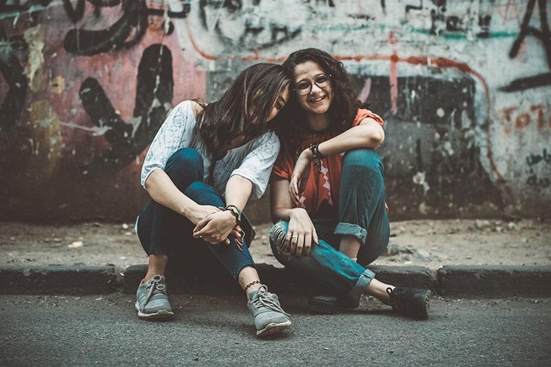 zwei Freundinnen, die sich aufeinander stützen und auf dem Bürgersteig sitzen
