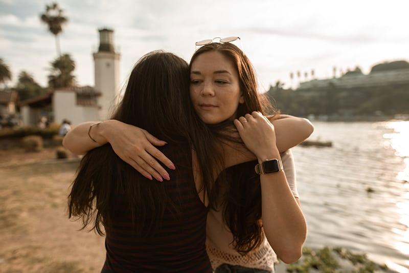 Zwei Freundinnen umarmen sich, während sie in der Nähe des Sees stehen