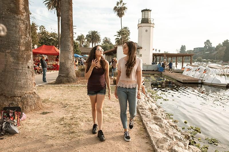 Zwei Freundinnen unterhalten sich beim Gehen in der Nähe des Sees