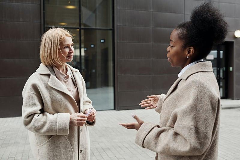 Zwei Kolleginnen unterhalten sich vor dem Gebäude