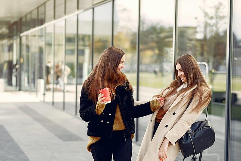 zwei lächelnde Freundinnen, die auf dem Zebrastreifen nahe dem Gebäude stehen