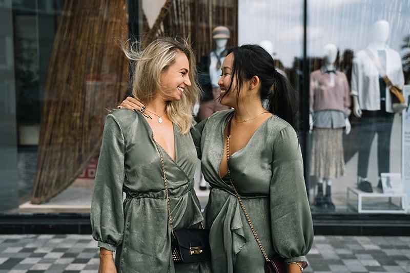 zwei lächelnde Freundinnen, die sich beim Umarmen ansehen