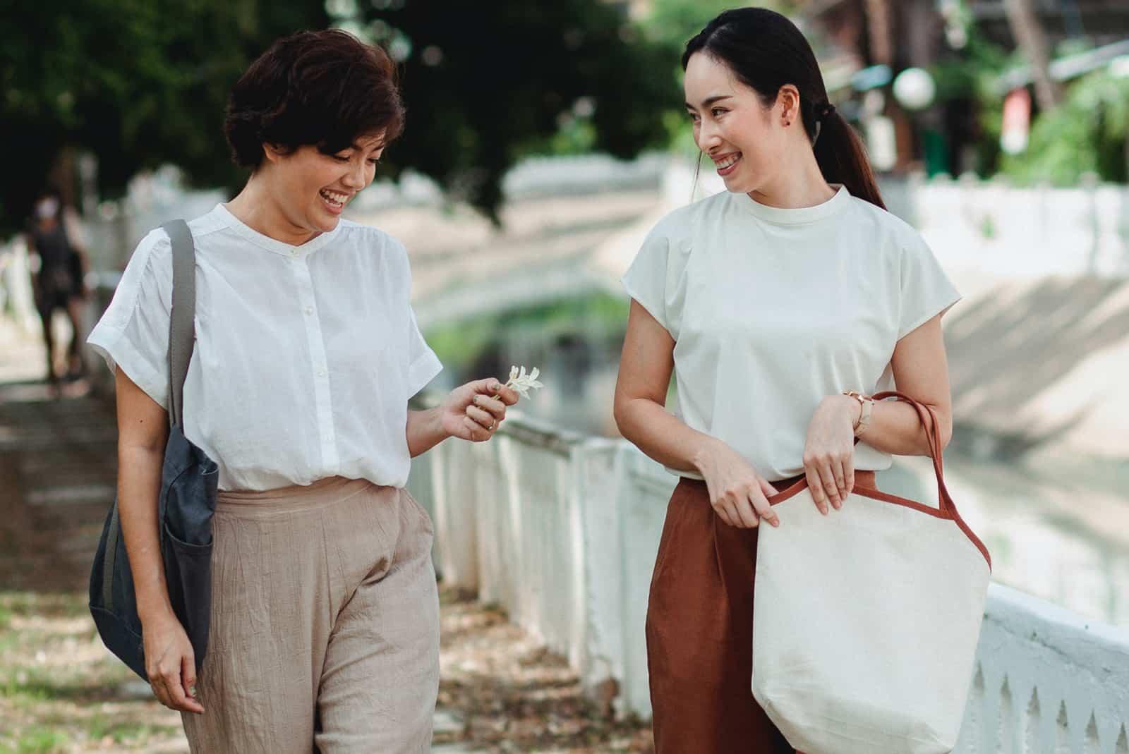 zwei lächelnde Freundinnen, die zusammen auf dem Bürgersteig gehen