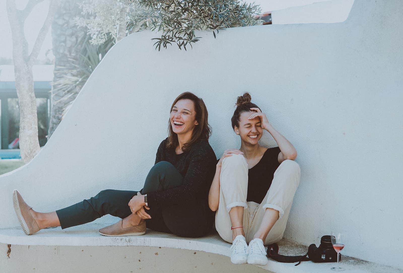 zwei lächelnde Freundinnen, die auf der Betonbank sitzen