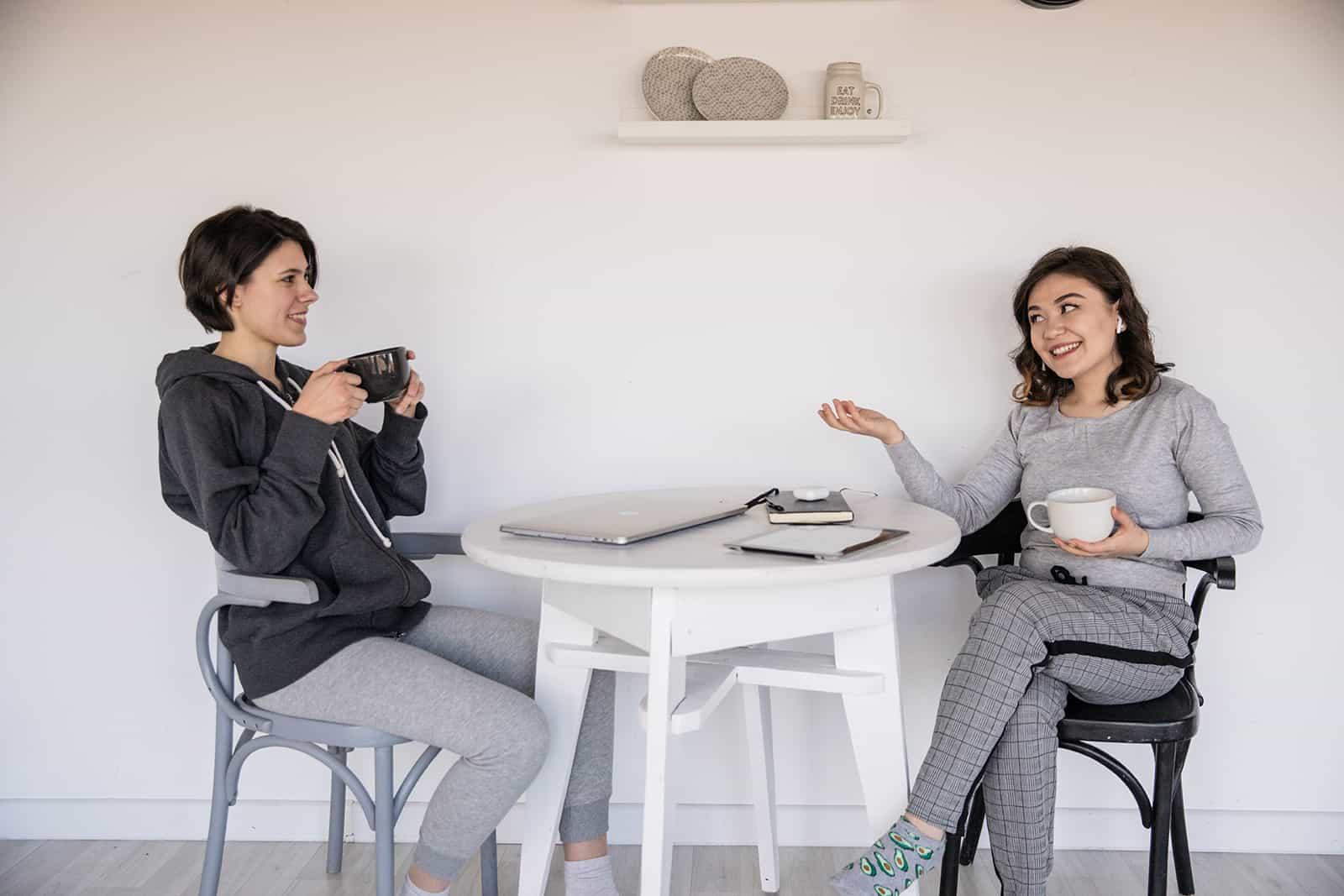 zwei positive Freundinnen, die sich unterhalten und gemeinsam Kaffee trinken
