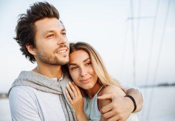 Ein glücklicher Mann umarmt eine lächelnde Frau