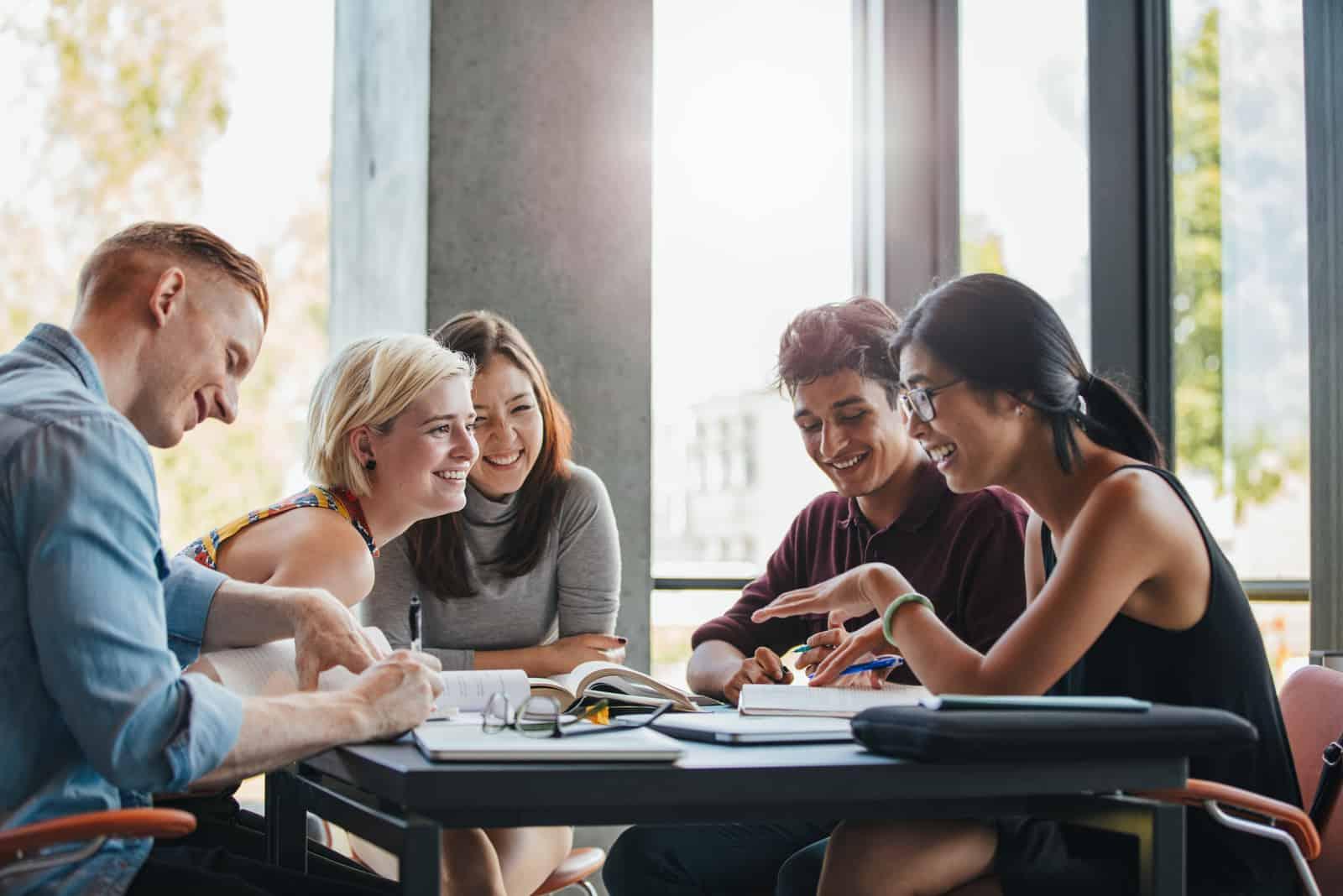 Am Tisch lacht und redet eine Gruppe junger Leute