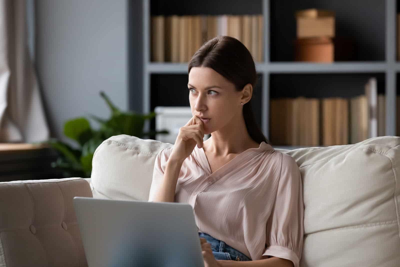 Auf dem Sofa denkt eine Frau nach und benutzt einen Laptop