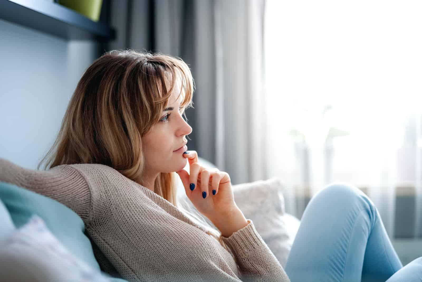 Auf der Couch sitzt die Blondine und denkt positiv