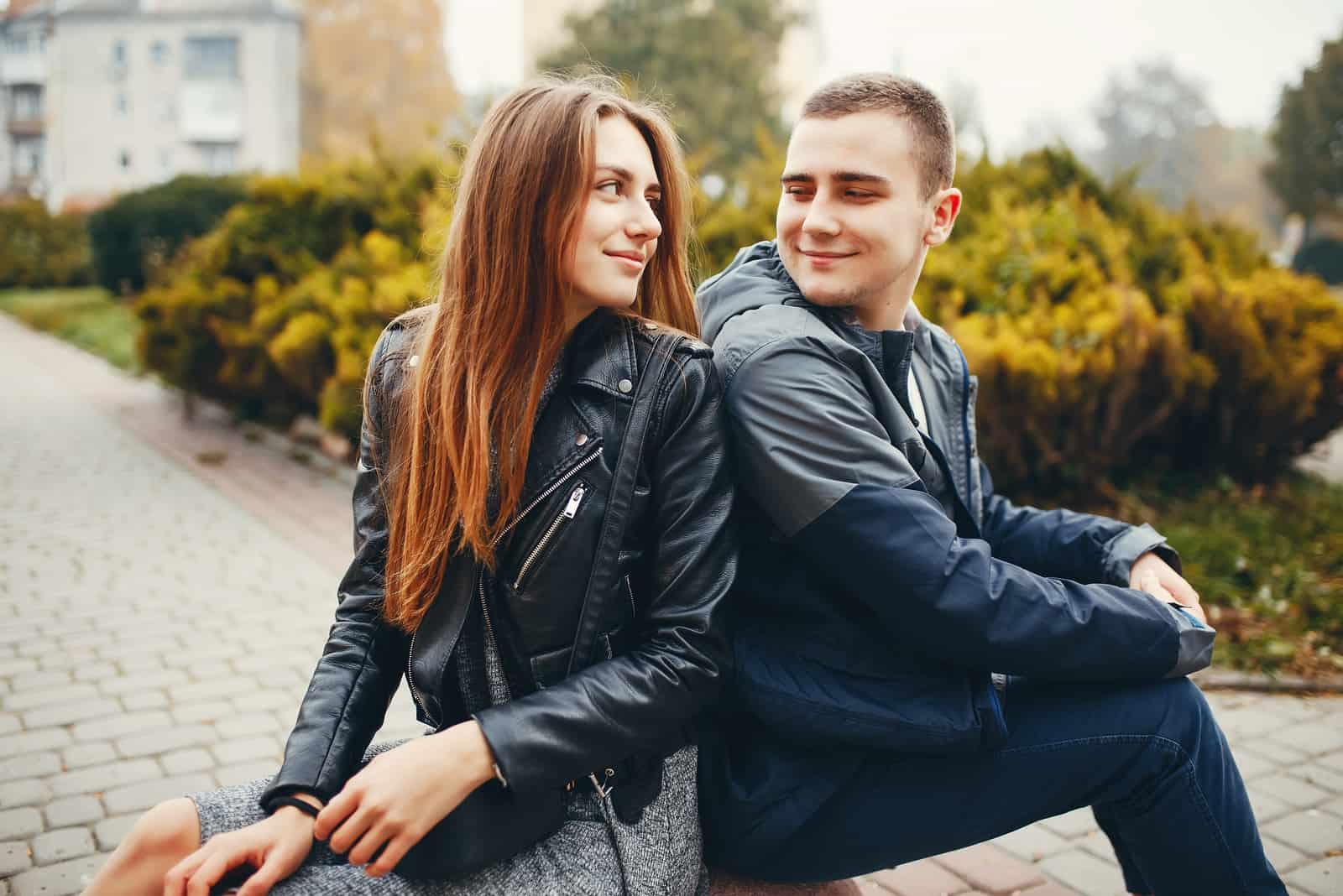 Auf der Parkbank sitzt ein lächelndes Paar und sie sehen sich an