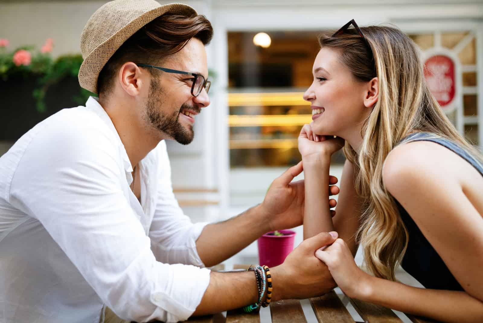 Auf der Terrasse des Cafés sitzt ein Liebespaar Händchen haltend