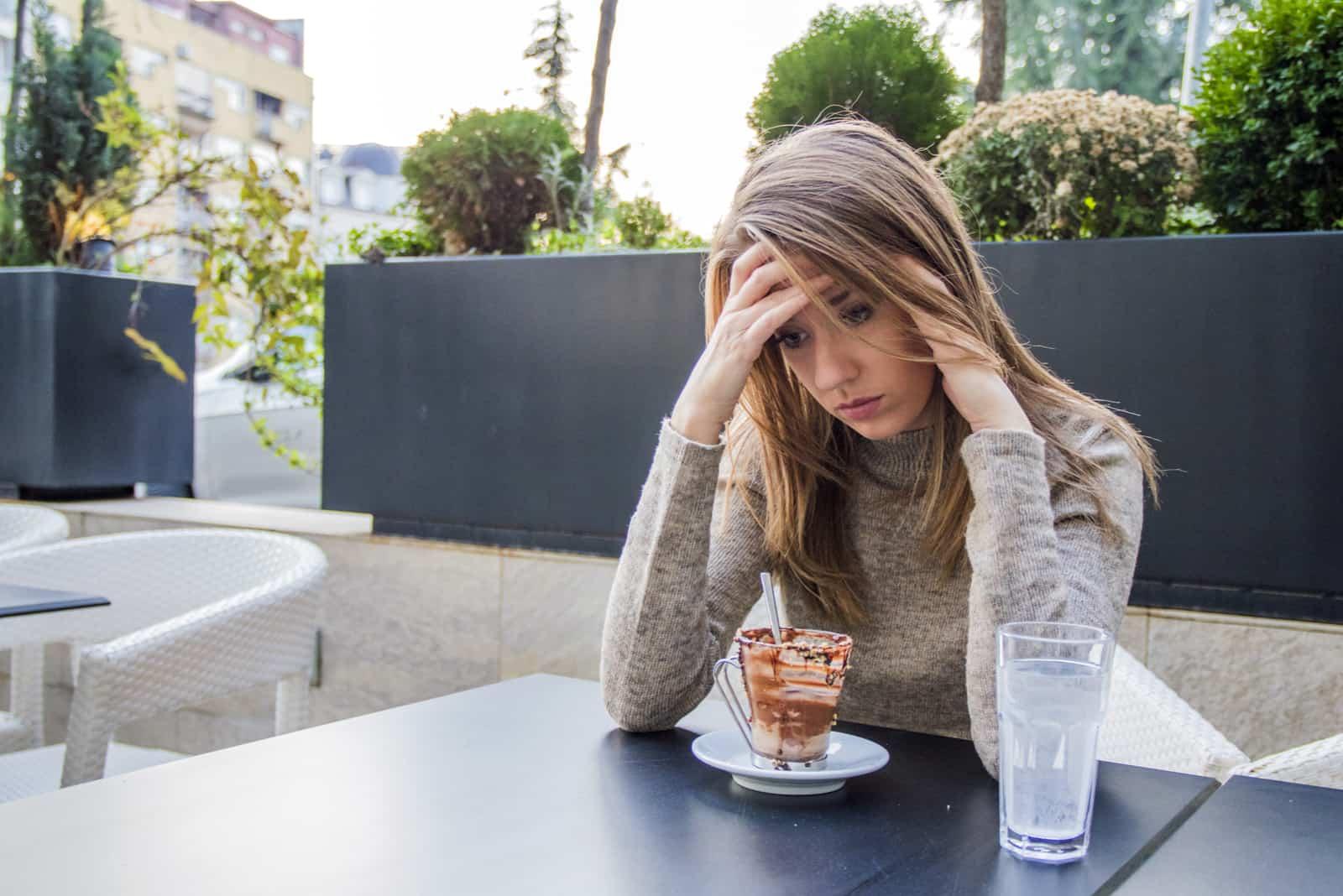 Auf der Terrasse des Cafés sitzt eine traurige Brünette
