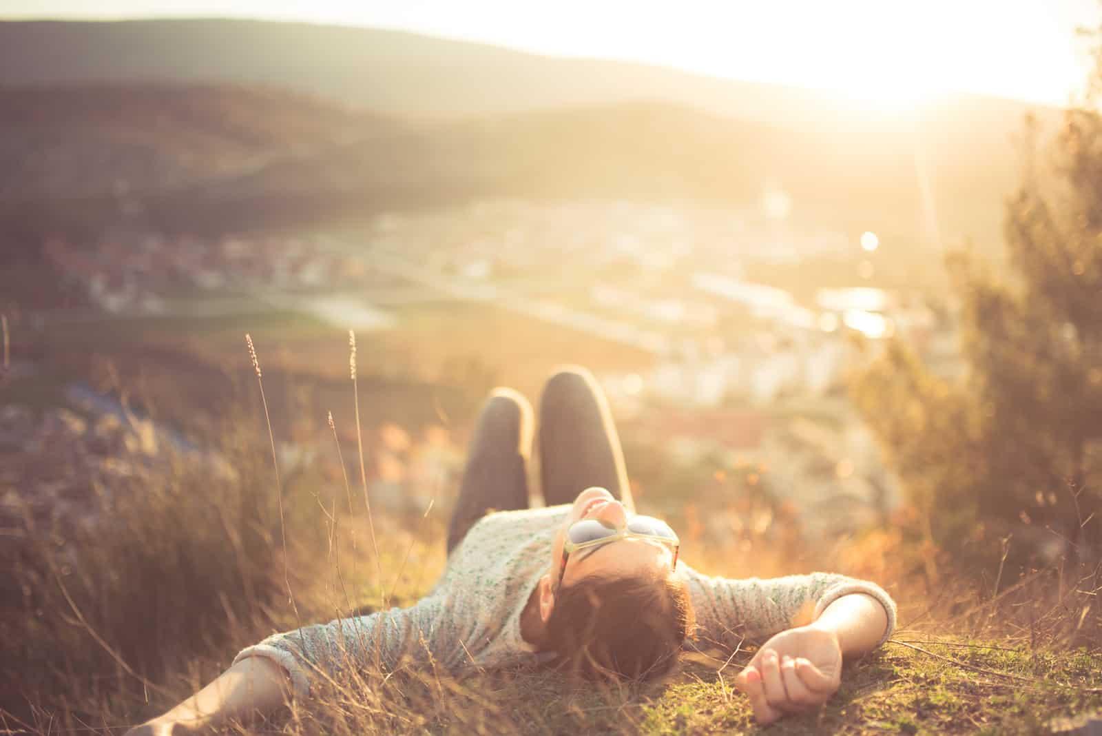 Auf einem Hügel im Gras liegt und ruht eine Frau