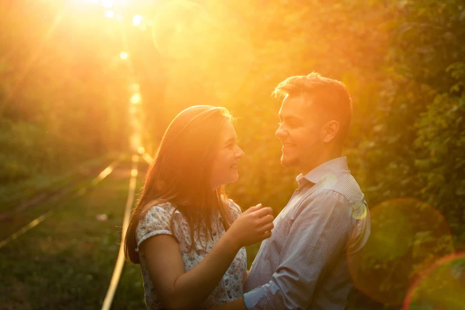 Bei Sonnenuntergang steht ein liebendes Paar draußen und umarmt sich