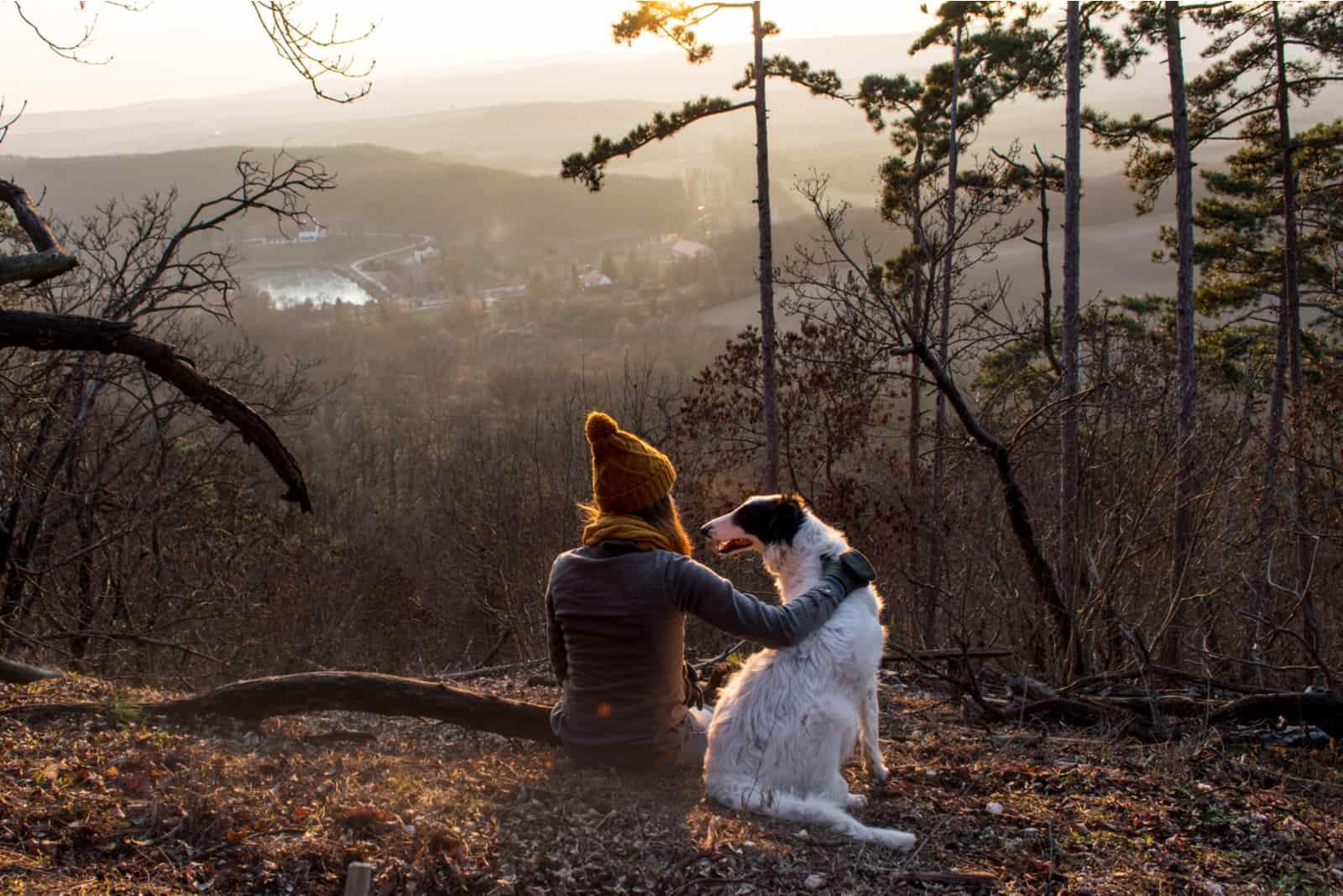 Das Mädchen ruht mit ihrem Hund in den Bergen
