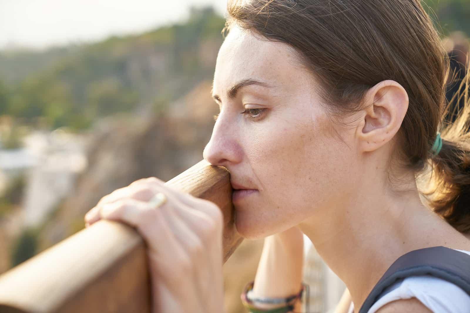 eine depressive Frau, die sich auf das Holzbrett stützte und nach unten schaute