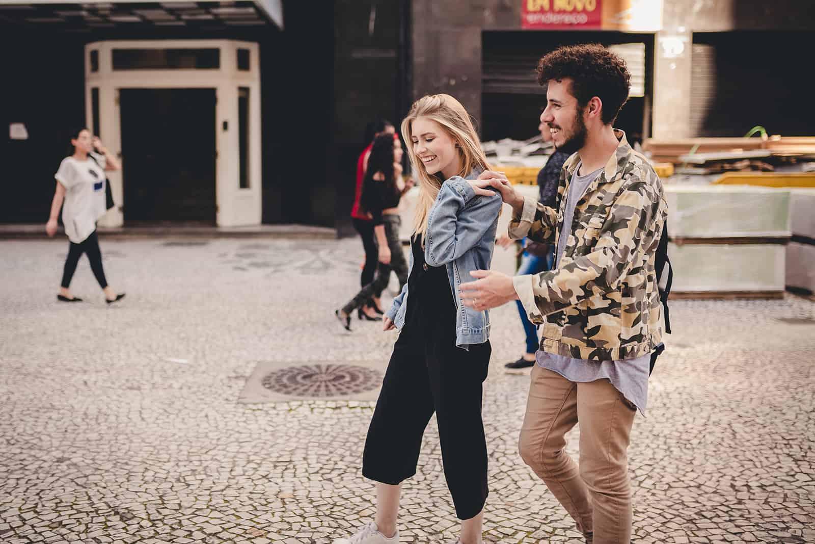 ein lächelndes Paar, das Hände hält, die auf der Straße gehen