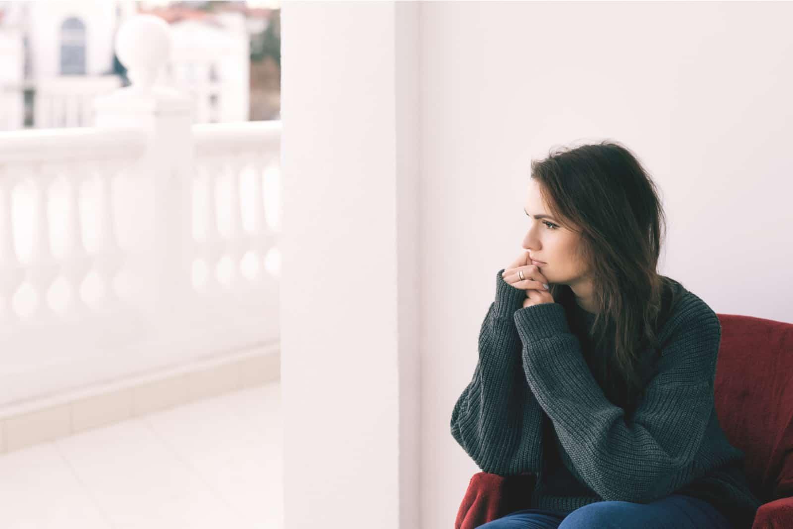 Draußen auf der Terrasse in einem Sessel sitzt eine besorgte Brünette
