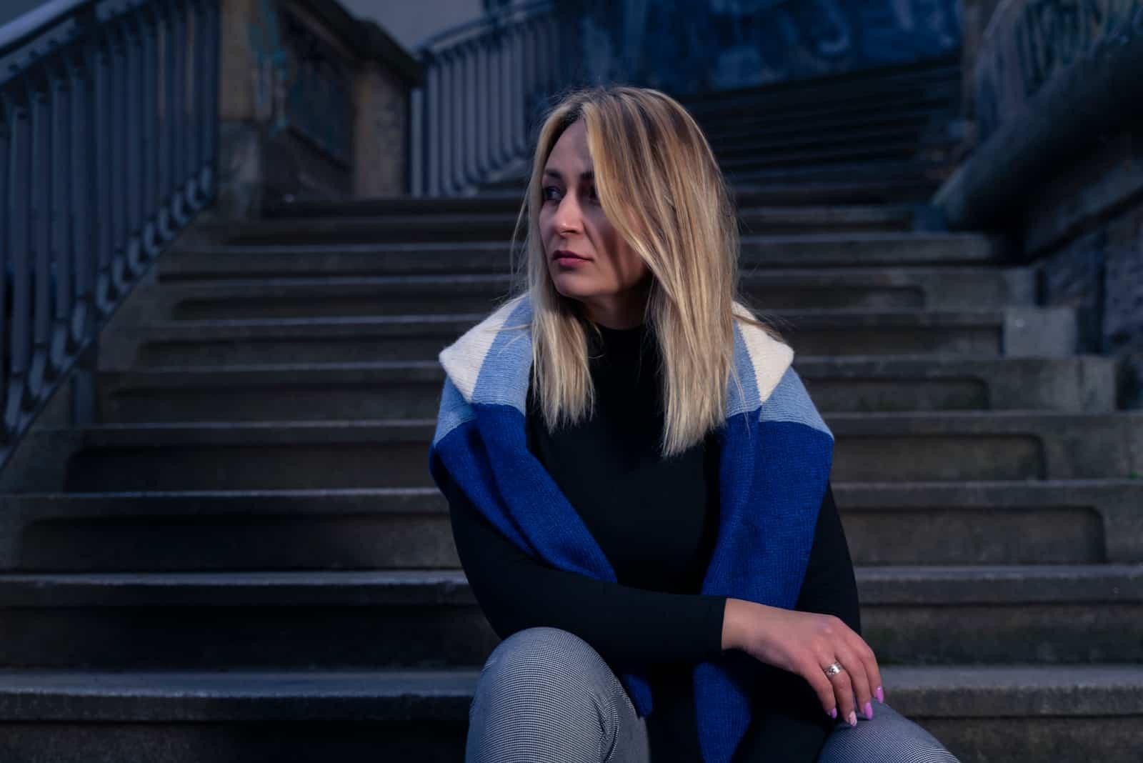 Draußen auf der Treppe sitzt eine traurige Blondine und denkt nach