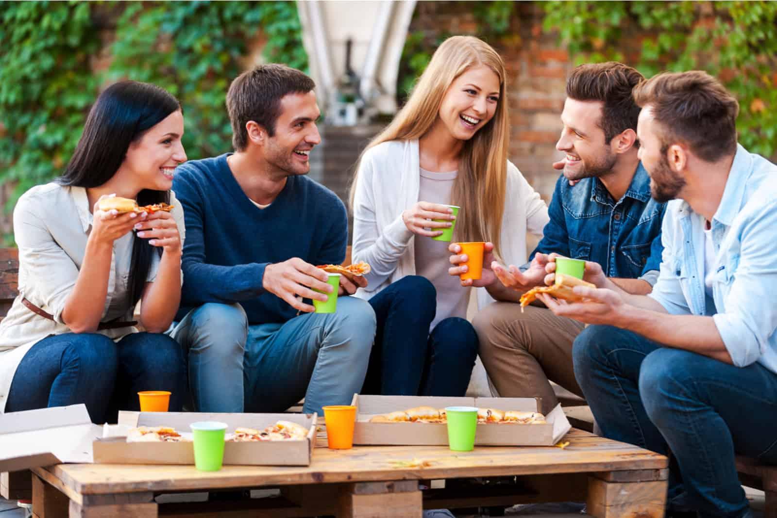 Draußen haben eine Gruppe von Freunden Spaß und essen Pizza