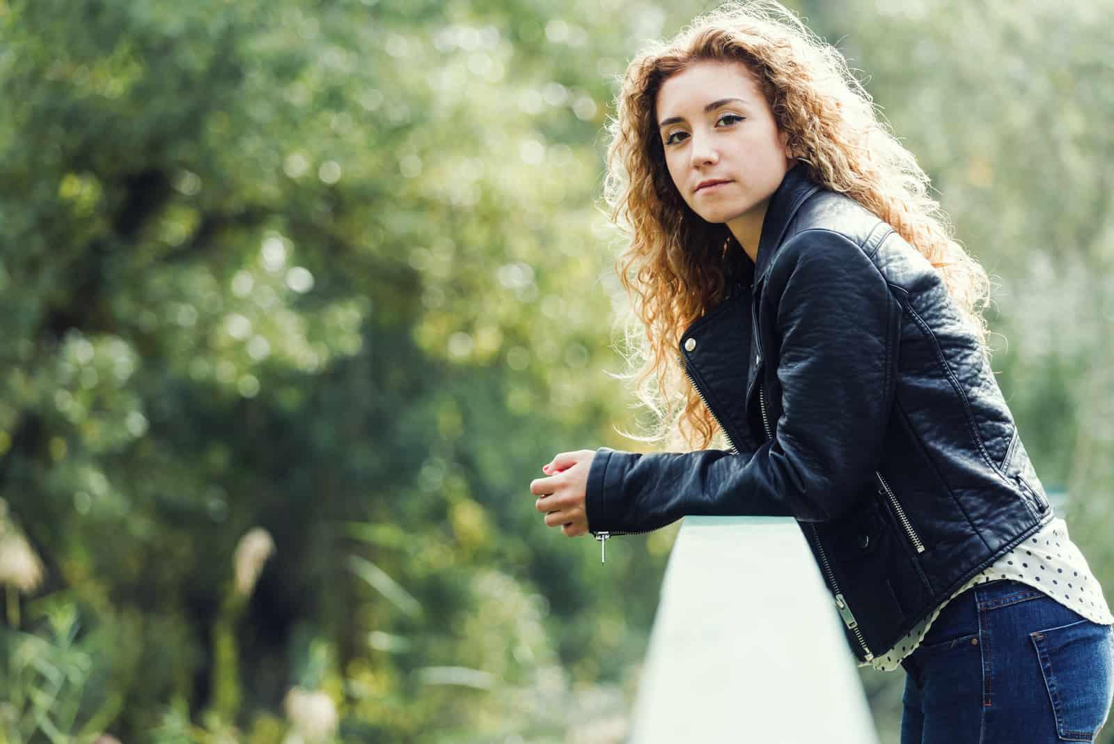 Draußen steht eine ernsthafte junge Frau, die sich gegen das Geländer lehnt