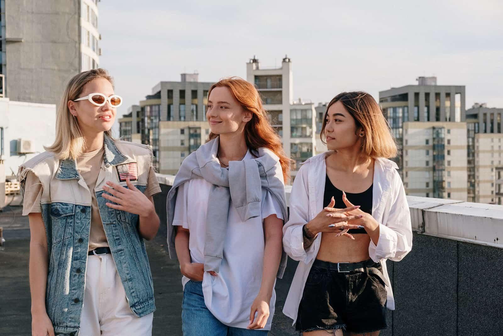 Drei Freundinnen unterhalten sich beim gemeinsamen Gehen auf dem Dach