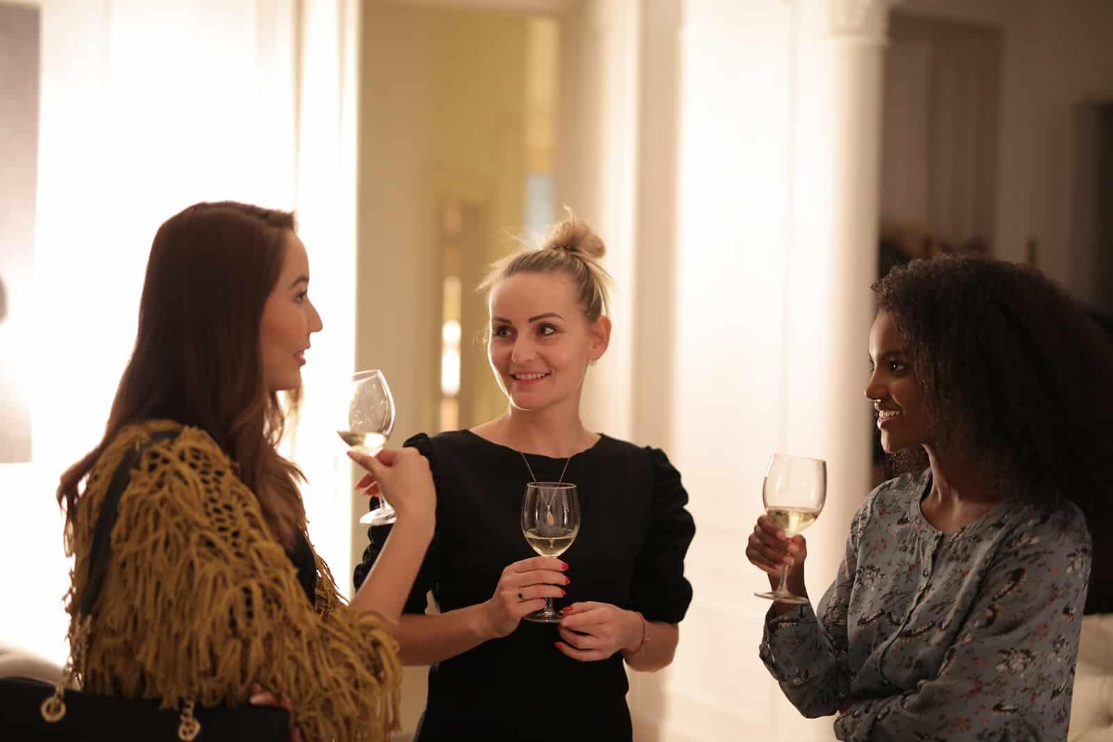 Drei Freundinnen unterhalten sich beim Weintrinken
