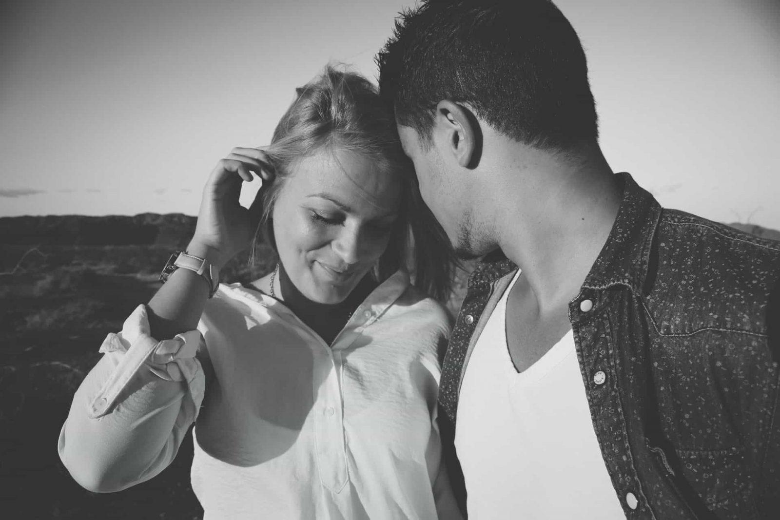 Ein Mann flüstert einer lächelnden Frau, die mit ihr flirtet, ein Kompliment zu