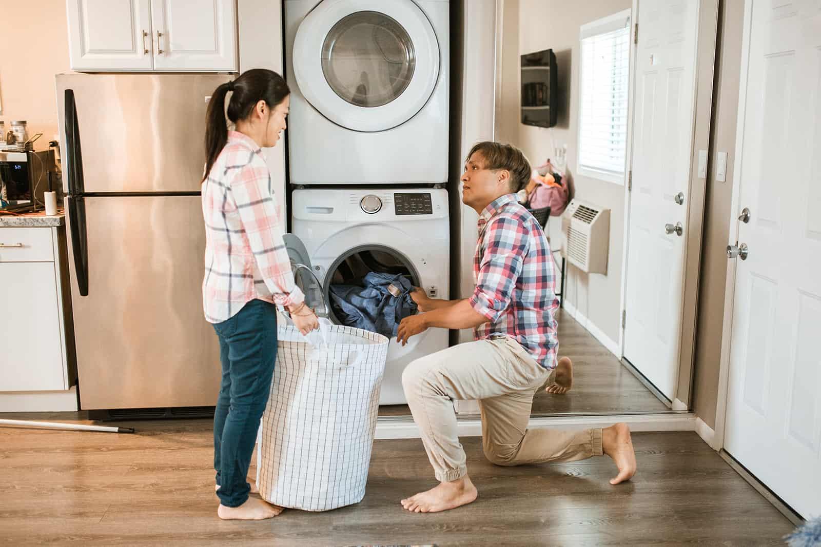 Ein Mann hilft ihrer Frau, Wäsche aus einer Waschmaschine zu holen in einen Korb