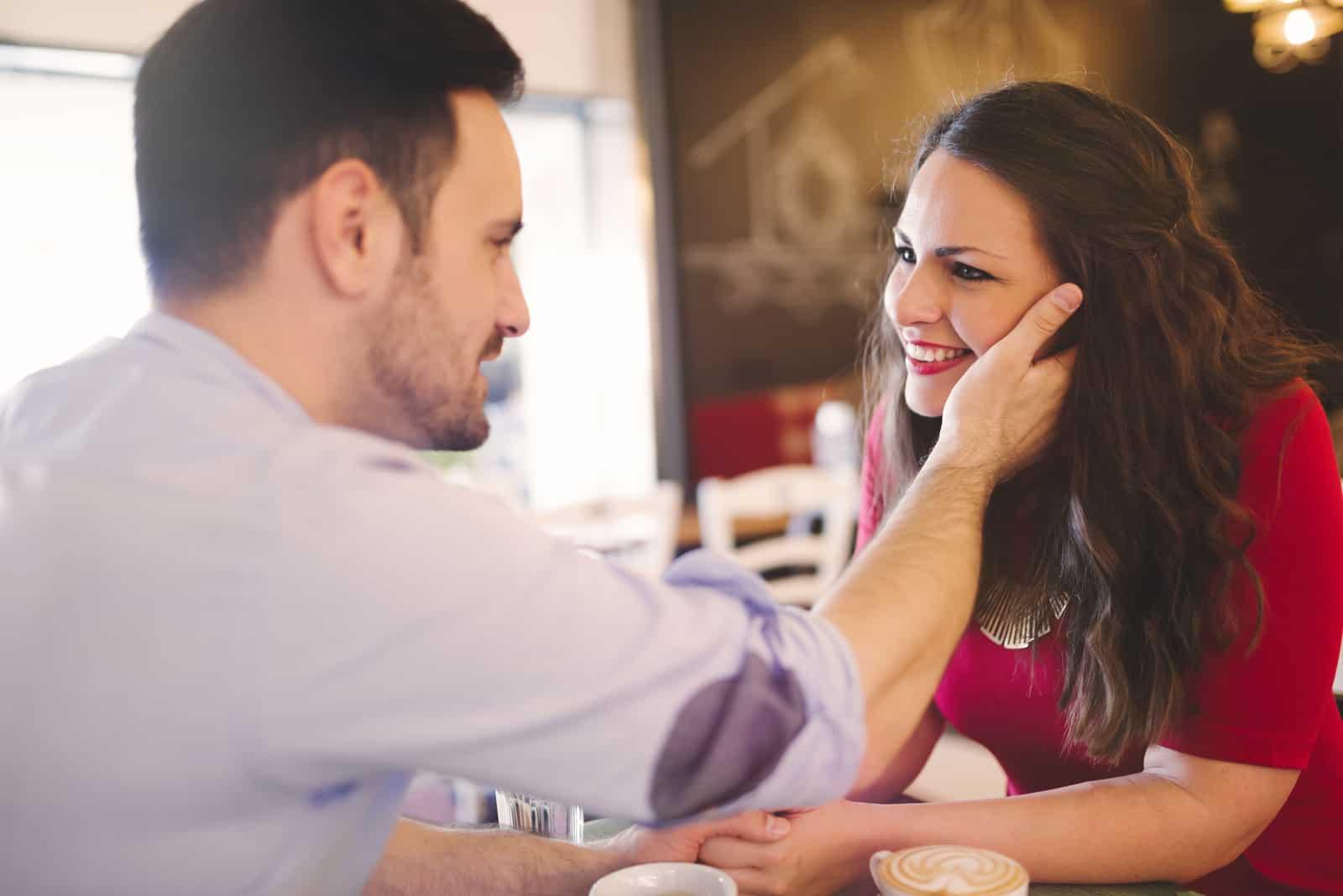 Ein Mann in einem Café streichelt das Gesicht einer lächelnden Frau