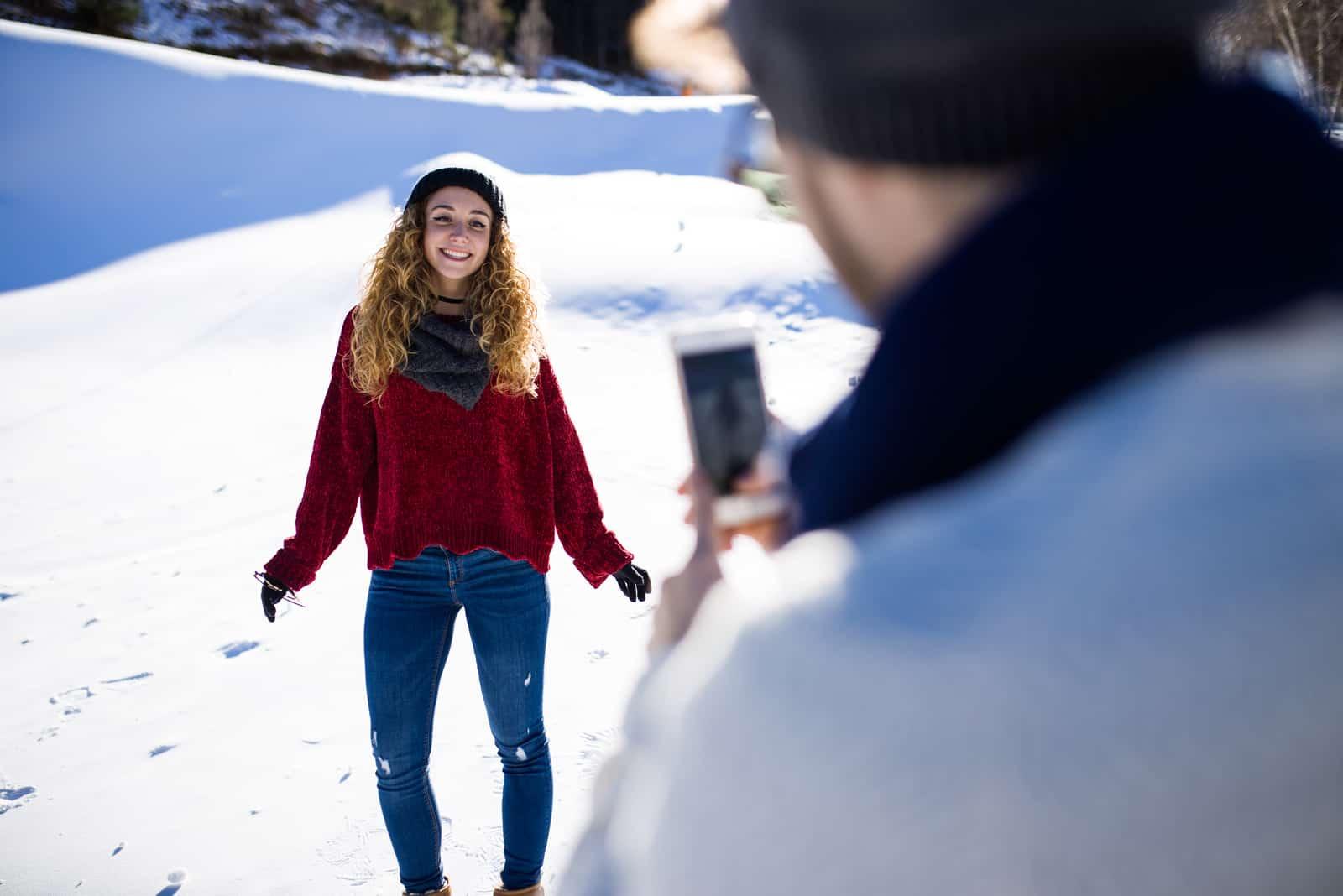 Ein Mann malt eine lächelnde Frau im Schnee