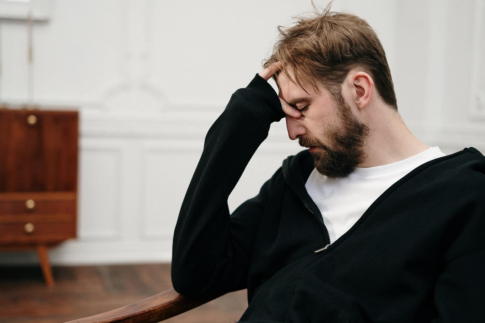Ein Mann mit Depressionen sitzt im Sessel und lehnt den Kopf an die Hand