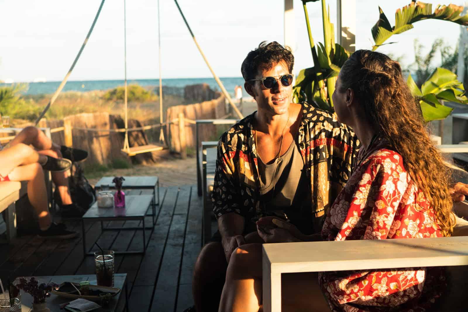 Ein Mann mit Sonnenbrille sitzt mit einer Frau im Café am Strand