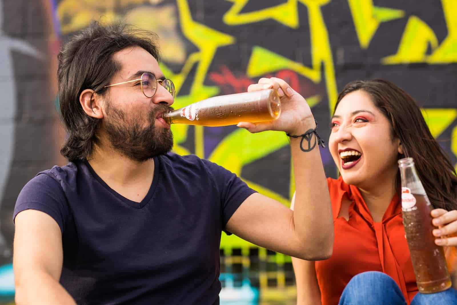 Ein Mann trinkt aus der Flasche in der Nähe der lächelnden Frau, die ihre Flasche mit einem Getränk hält
