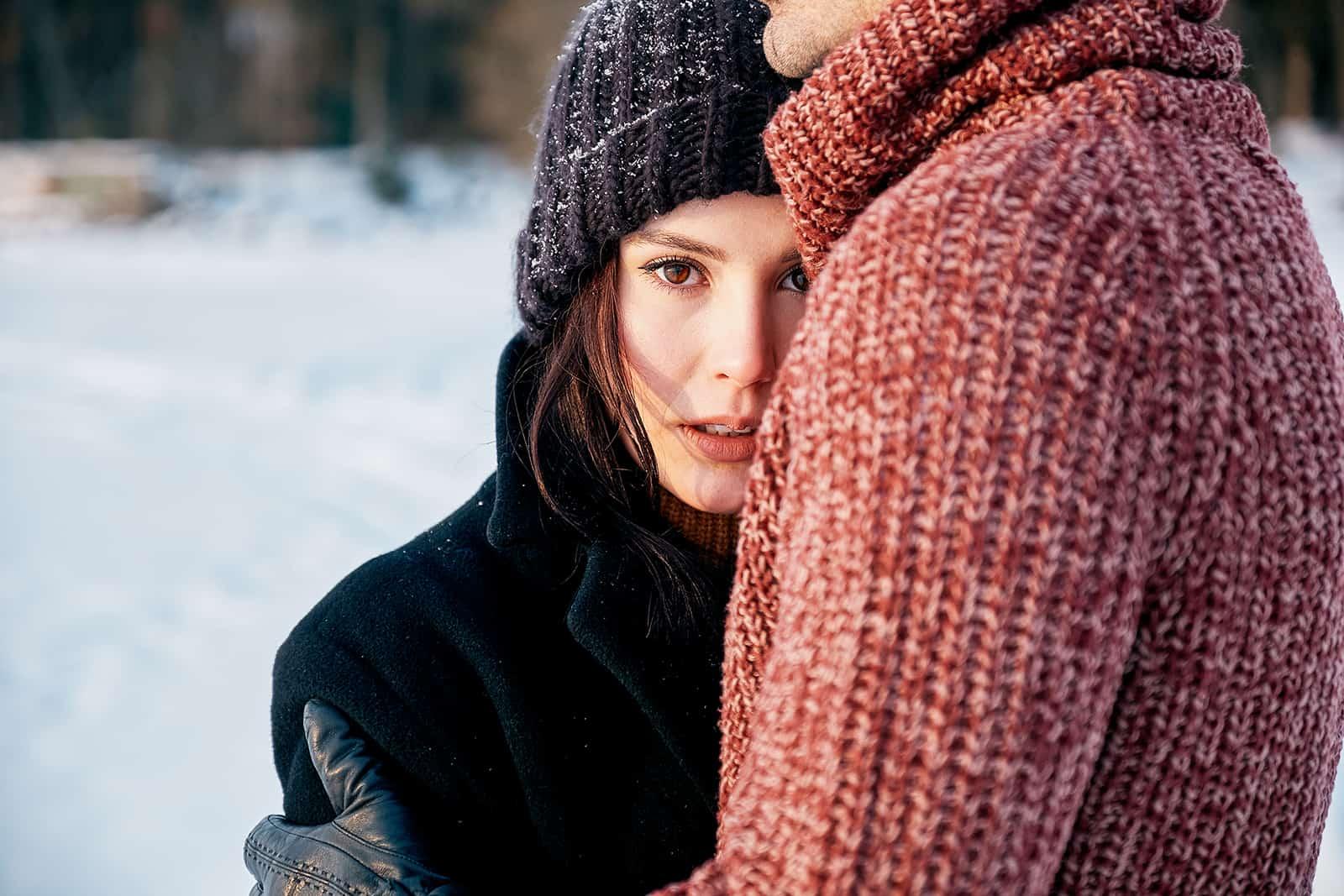 Ein Mann umarmt eine verwirrte Frau, während er auf dem Schnee steht