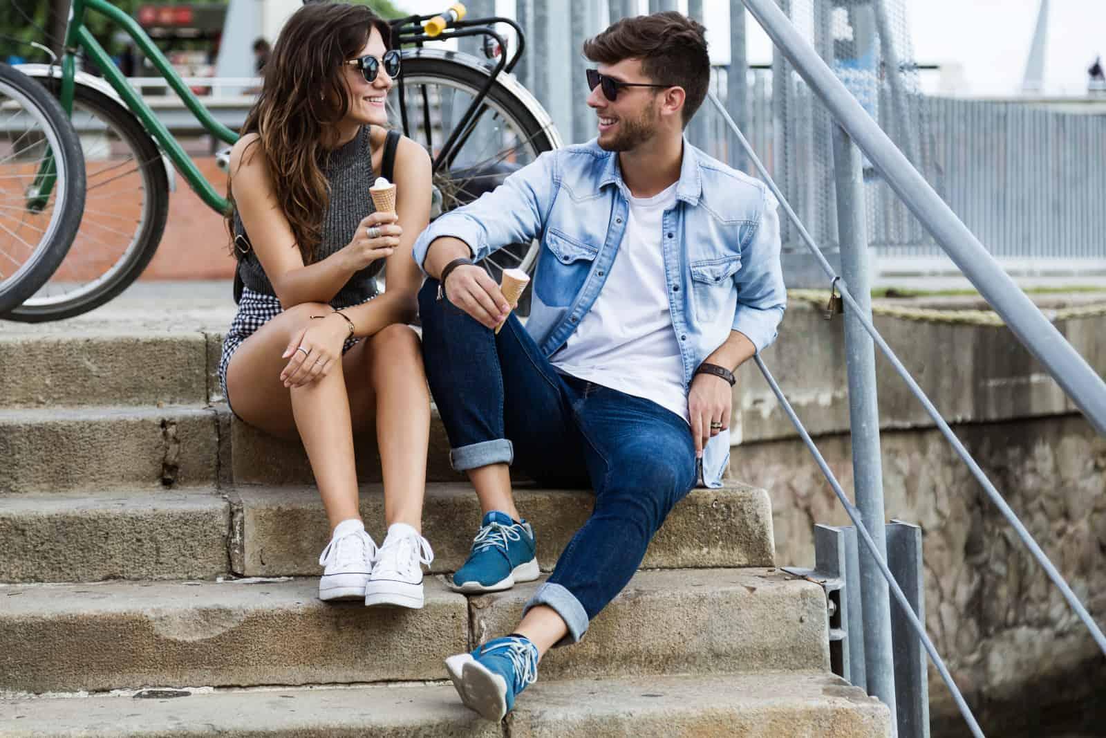 Ein Mann und ein Mädchen sitzen auf dem Boden und essen Eis