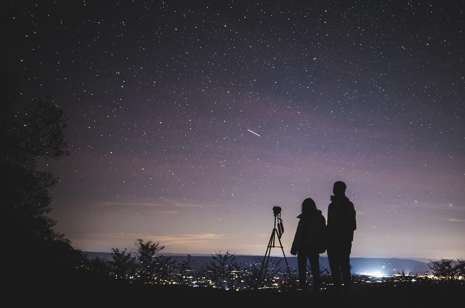 Ein Mann und eine Frau beobachten Sterne außerhalb der Stadt