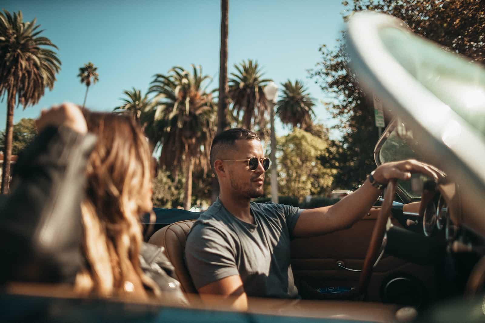 Ein Mann und eine Frau fahren an einem sonnigen Tag in einem Auto