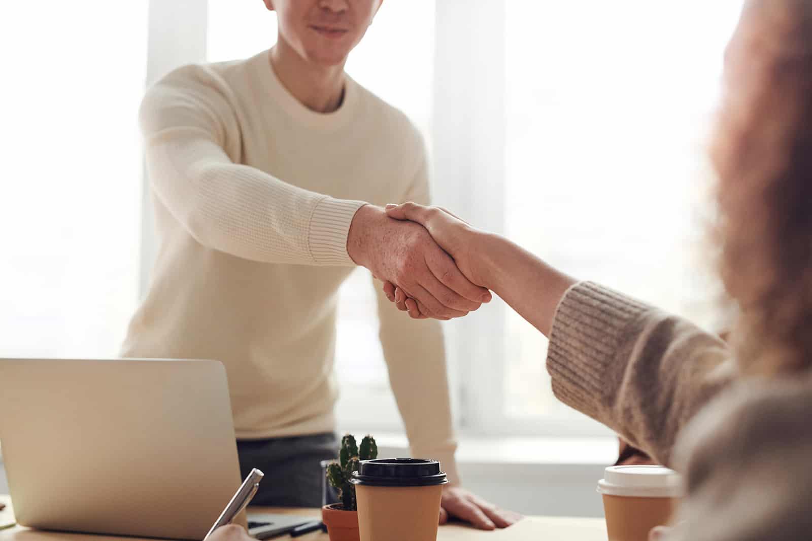Ein Mann und eine Frau schütteln sich im Büro die Hände über den Tisch