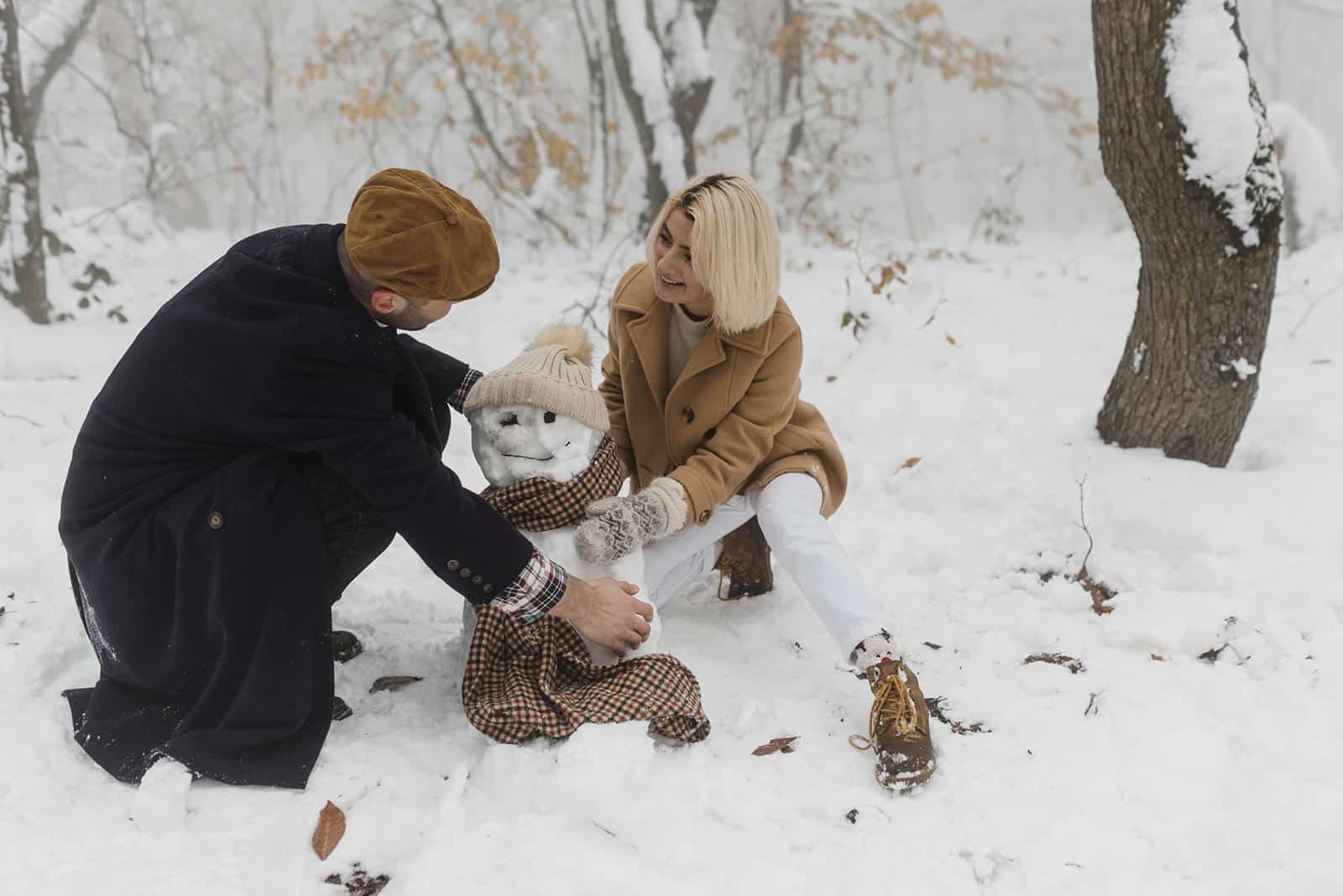 Ein Mann und eine Frau machen einen Schneemann im Park