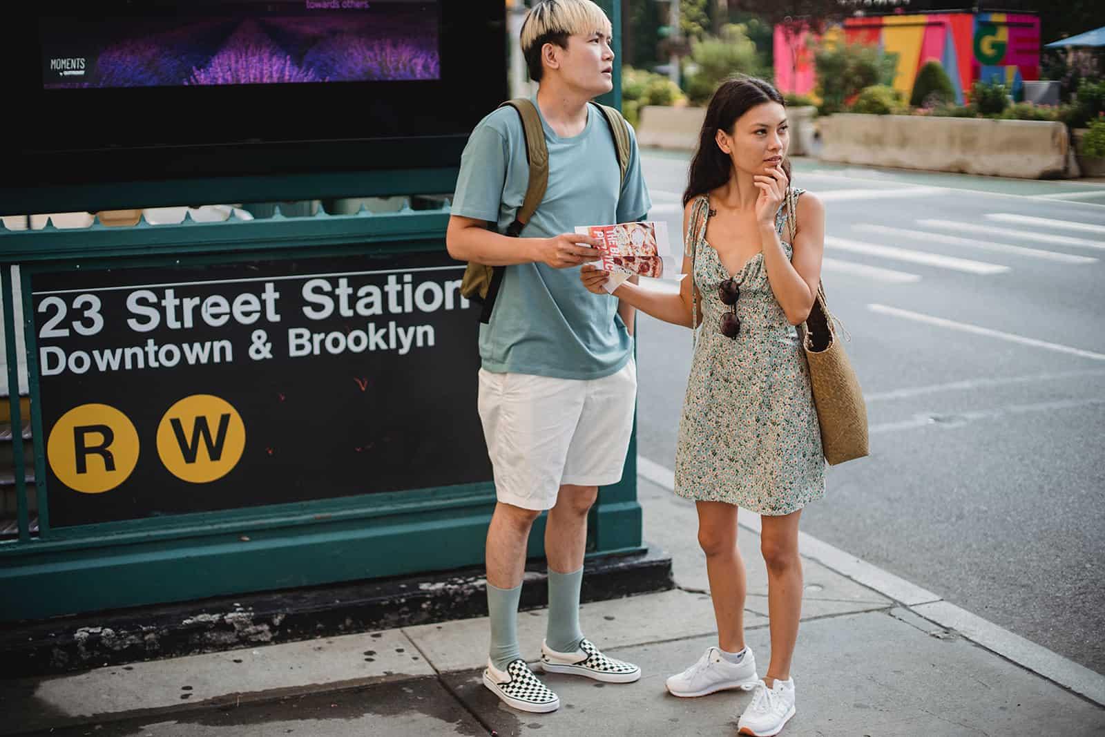 Ein Mann und eine Frau sehen sich um und halten einen Stadtplan